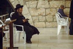 Hombre judío que se sienta en una silla y que sostiene el libro de la biblia, rogando en la pared que se lamenta sagrada, pared o imágenes de archivo libres de regalías
