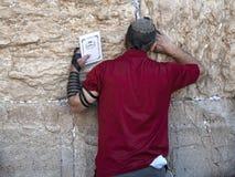 Hombre judío shirted rojo que lleva a cabo el viejo testamento y que ruega en la pared que se lamenta, Jerusalén/Israel fotografía de archivo libre de regalías