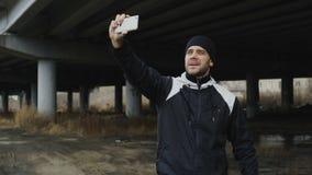 Hombre juguetón feliz que toma el retrato del selfie con smartphone después de entrenar en la ubicación urbana del aire libre en  almacen de video