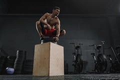Hombre juguetón joven que descansa después de ejercicio del salto de la caja en el gimnasio imagen de archivo