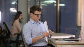 Hombre juguetón que hace el avión del papel, enviándolo al colega femenino asiático, rotura almacen de metraje de vídeo
