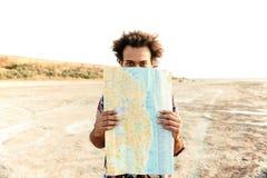Hombre juguetón que se coloca y que oculta detrás de mapa al aire libre Fotos de archivo libres de regalías
