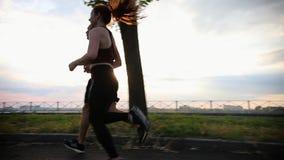 Hombre juguetón y mujer que corren en la trayectoria en la última hora de la tarde metrajes