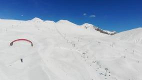hombre 4k en el paracaídas en montañas del invierno almacen de video