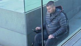 hombre 4k en la silla de ruedas eléctrica usando una rampa - cacerola seguir el movimiento almacen de video