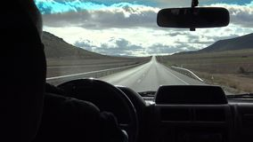 hombre 4K que conduce un coche en largo camino a través de campo hermoso en España metrajes