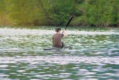 Hombre kayaking en el río de la inundación Imagenes de archivo