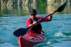 Hombre kayaking en la puesta del sol del río Fotografía de archivo