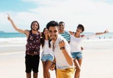 Hombre latino de risa con animar a adultos jovenes en la playa Foto de archivo libre de regalías