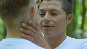 Hombre latino hermoso que frota ligeramente el brazo del socio, proximidad de los pares, fecha romántica al aire libre almacen de video