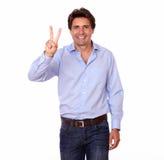 Hombre latino hermoso que gesticula la muestra de la victoria Foto de archivo libre de regalías