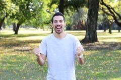 Hombre latino joven que hace gesto del éxito en un parque Foto de archivo