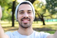 Hombre latino joven que toma un selfie en un parque Imagenes de archivo