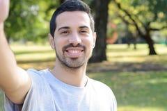Hombre latino joven que toma un selfie en un parque Fotografía de archivo