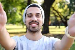 Hombre latino joven que toma un selfie en un parque Imagen de archivo