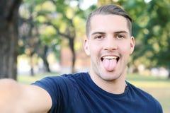 Hombre latino joven que toma un selfie en un parque Foto de archivo