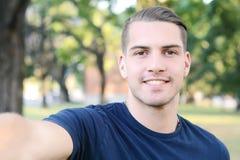 Hombre latino joven que toma un selfie en un parque Fotos de archivo