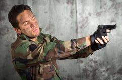 Hombre latino militar del soldado que señala un arma Imagen de archivo