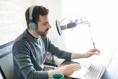 Hombre latino que recibe la radio en línea foto de archivo libre de regalías