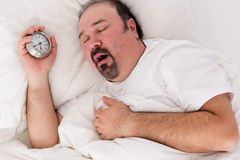 Hombre letárgico que bosteza como él lucha para despertar Foto de archivo