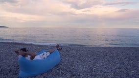 Hombre libre que se relaja en la playa, disfrutando de la opinión del paisaje marino, teniendo resto el vacaciones almacen de video