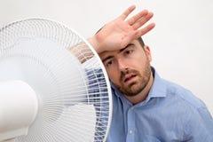 Hombre limpiado con un chorro de agua que siente caliente delante de una fan Fotos de archivo