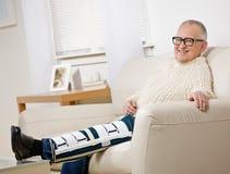Hombre lisiado con la paréntesis de la pierna que se sienta en el sofá Imagen de archivo libre de regalías
