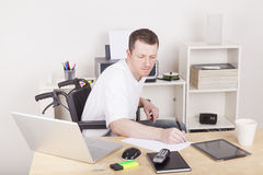 Hombre lisiado en oficina de la silla de ruedas en casa Imágenes de archivo libres de regalías