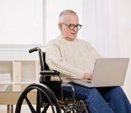Hombre lisiado en sillón de ruedas en la computadora portátil Imagen de archivo libre de regalías
