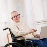 Hombre lisiado en sillón de ruedas usando de la tarjeta de crédito Foto de archivo libre de regalías