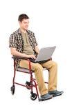 Hombre lisiado joven en una silla de ruedas que trabaja en una computadora portátil Foto de archivo libre de regalías