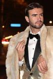 Hombre llamativo elegante, de moda con el traje de oro, corbata de lazo y abrigo de pieles al aire libre Imagenes de archivo