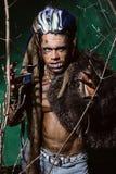 Hombre lobo con los clavos largos y los dientes torcidos entre las ramas de Fotos de archivo libres de regalías