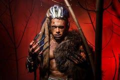 Hombre lobo con los clavos largos y los dientes torcidos entre las ramas de Fotografía de archivo libre de regalías