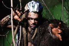 Hombre lobo con los clavos largos y los dientes torcidos entre las ramas de Fotos de archivo