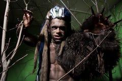 Hombre lobo con los clavos largos y los dientes torcidos entre las ramas de Imágenes de archivo libres de regalías