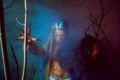 Hombre lobo con los clavos largos y los dientes torcidos entre las ramas de Fotografía de archivo