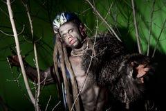 Hombre lobo con los clavos largos y los dientes torcidos entre las ramas de Foto de archivo libre de regalías