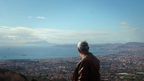 Hombre local caucásico mayor hermoso feliz que disfruta del panorama escénico increíble de la visión de Nápoles de la cámara lent almacen de video