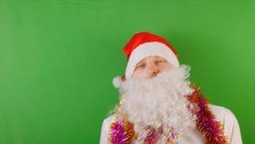 Hombre loco que lleva el sombrero de Papá Noel con la barba blanca, el Año Nuevo 2019 y la Navidad, en llave verde de la croma metrajes