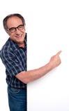 Hombre madurado causal que señala el dedo en el cartel Imagenes de archivo