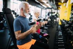 Hombre maduro apto feliz en gimnasio que se resuelve para permanecer sano fotos de archivo