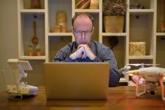 Hombre maduro con el abejón y ordenador portátil en el comedor en casa Fotografía de archivo