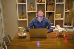 Hombre maduro con el abejón y ordenador portátil en el comedor en casa Imagen de archivo