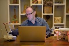 Hombre maduro con el abejón y ordenador portátil en el comedor en casa Fotos de archivo