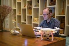 Hombre maduro con el abejón y ordenador portátil en el comedor en casa Imágenes de archivo libres de regalías