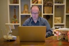 Hombre maduro con el abejón y ordenador portátil en el comedor en casa Fotos de archivo libres de regalías
