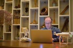Hombre maduro con el abejón y ordenador portátil en el comedor en casa Imagen de archivo libre de regalías