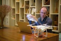 Hombre maduro con el abejón y ordenador portátil en el comedor en casa Fotografía de archivo libre de regalías