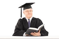 Hombre maduro con el libro de lectura del sombrero de la graduación asentado en la tabla imagenes de archivo
